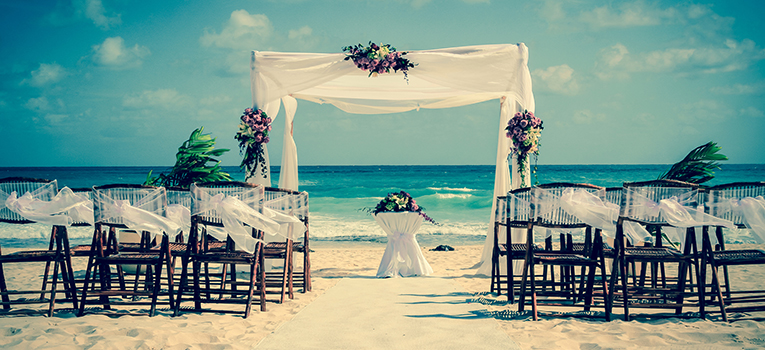 Allianz Global Assistance - A beach prepared for a destination wedding featuring a white canopy, flowers and chairs set up facing the beach for a wedding abroad.